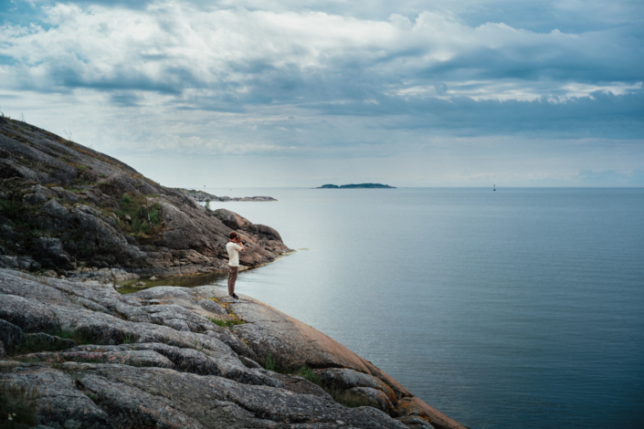 Man standing on a cliff, sea, clouds