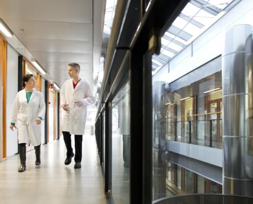 Two researchers walking in Biomedicum