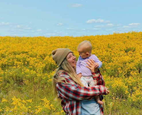 Mother holding a baby, yellow flower field in the background