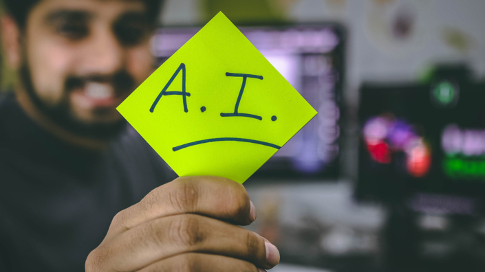 Man holding a post it that says A.I.