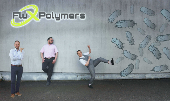 Flux Polymers team members with company logo and bacteria photoshopped