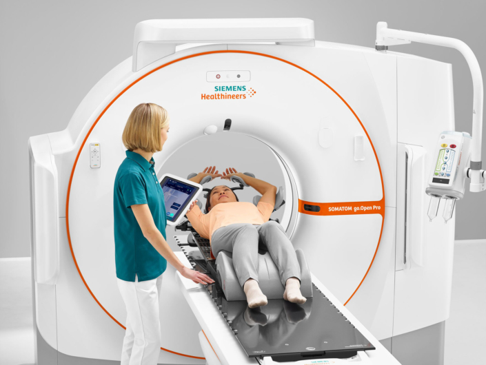 A patient lying in a CT scanner, healthcare professional looking after