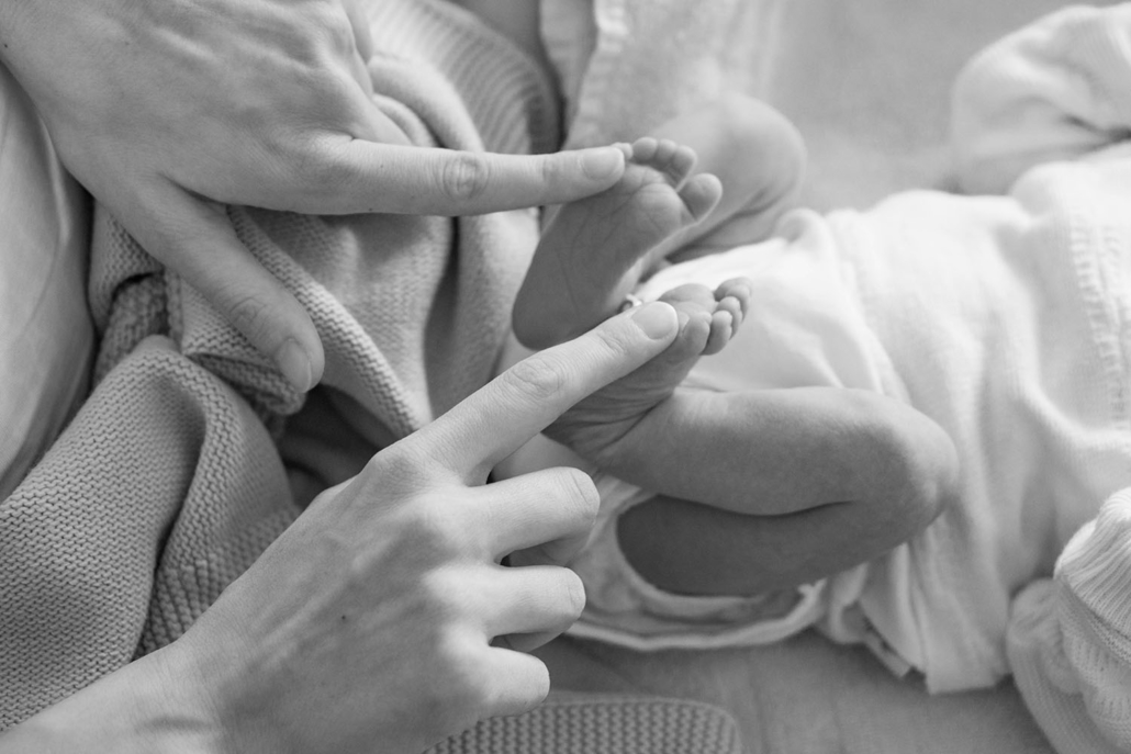 Newborn's feet and mother's fingers