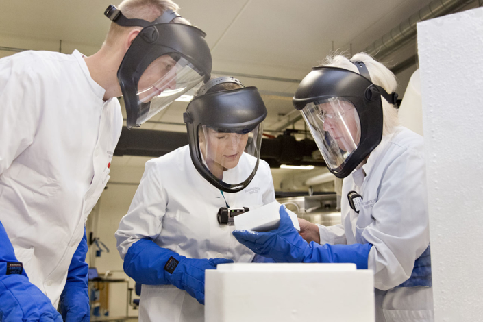 Three researchers with visors and gloves